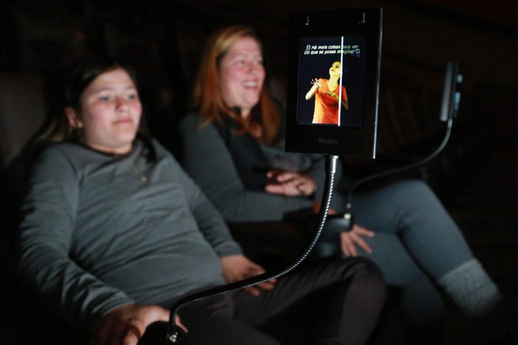 Mãe e filho assistem filme em um cinema com recursos inclusivos