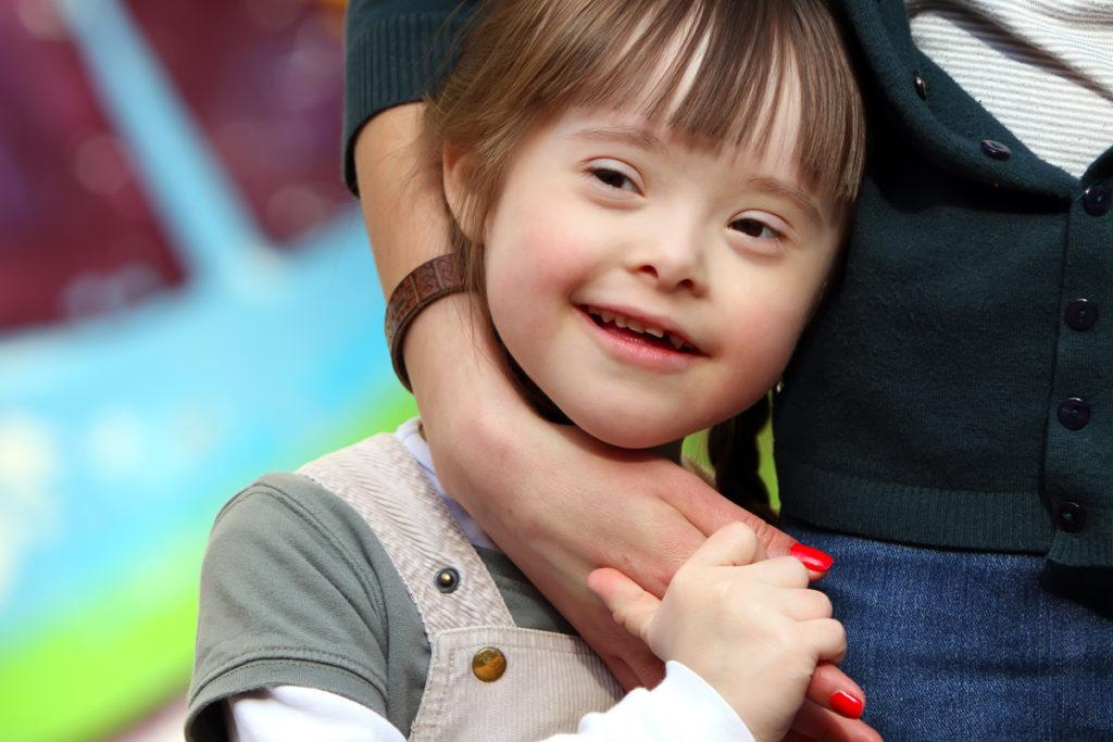 criança com Sindrome de Down abraçada a professora