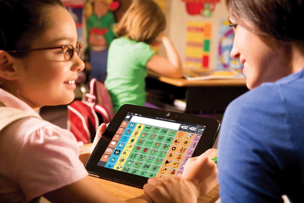 Aluna se comunica com professora através de tópicos em um dispositivo de comunicação alternativa
