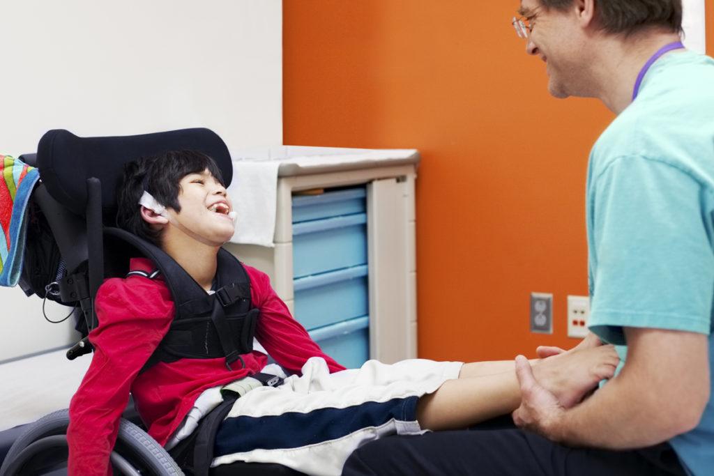 Menino com deficiência e seu fisioterapeuta, cuidado ao coronavírus