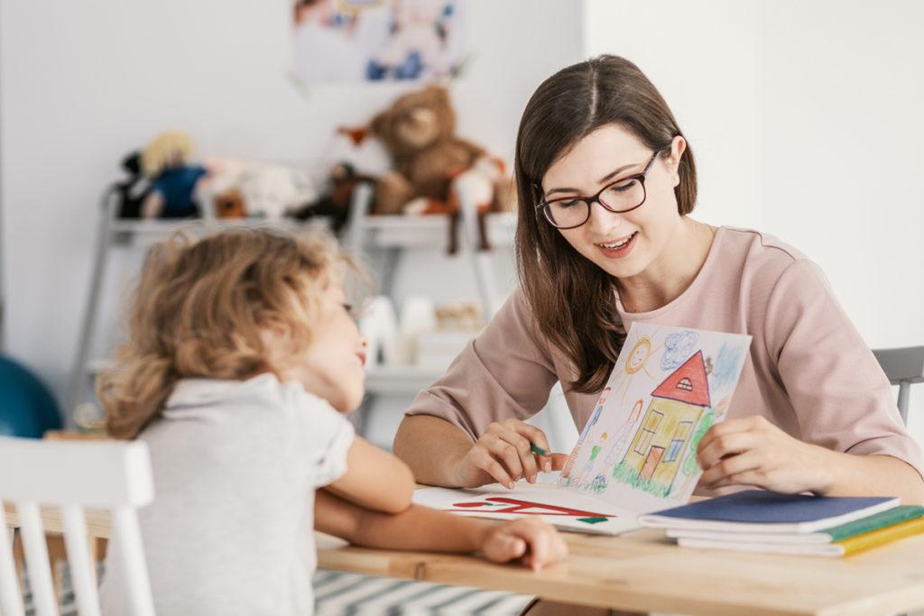 Neste momento de coronavírus, mãe segurando o desenho de uma casa e mostrando pra filha que está em sua frente