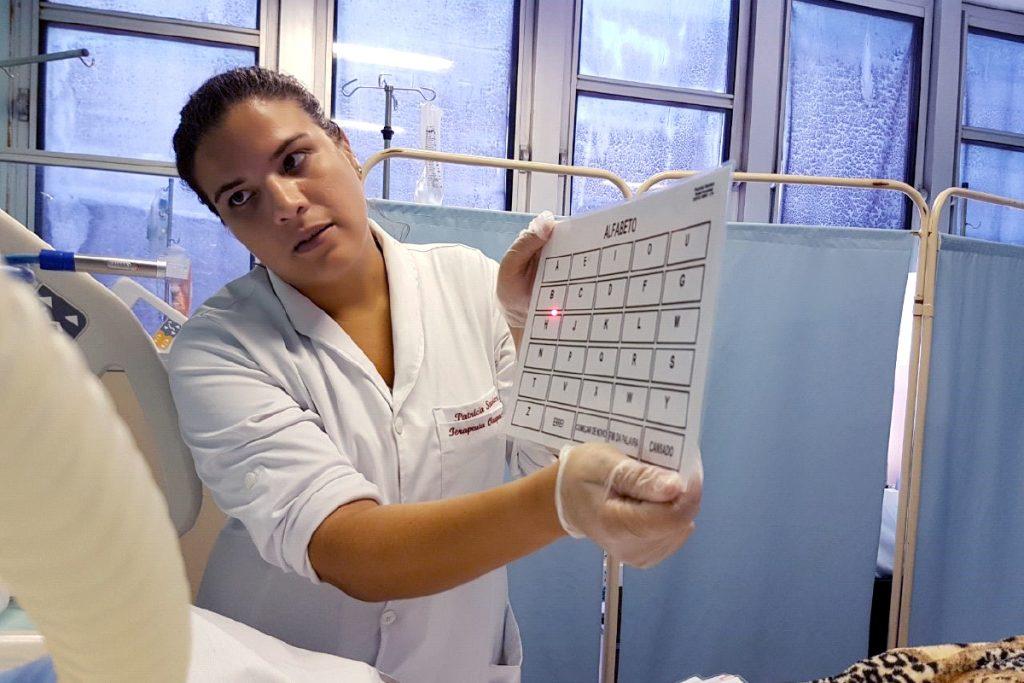 Terapeuta Ocupacional intermediando a comunicação de um paciente internado na UTI com prancha de comunicação do alfabeto e ponteira a laser para cabeça
