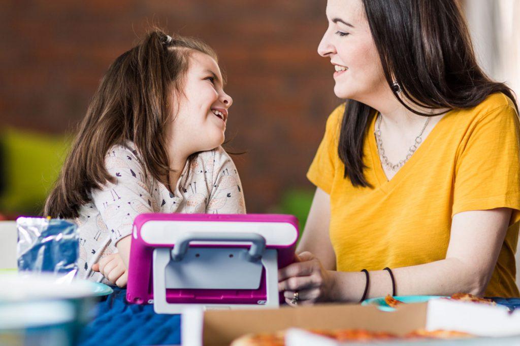 mãe e filha usando dispositivo de comunicação alternativa