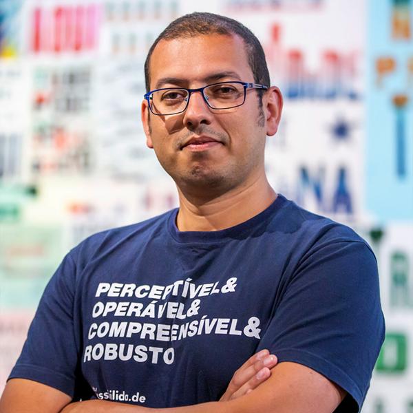 """foto de Marcelo Sales, vestindo camiseta azul com escritos em branco: """"perceptível & operável & compreensível &  robusto"""