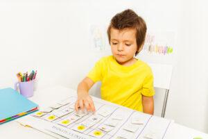 Criança autista de camiseta amarela, montando calendário de atividades