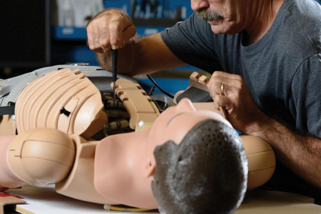homem fazendo manutenção preventiva em simulador de paciente