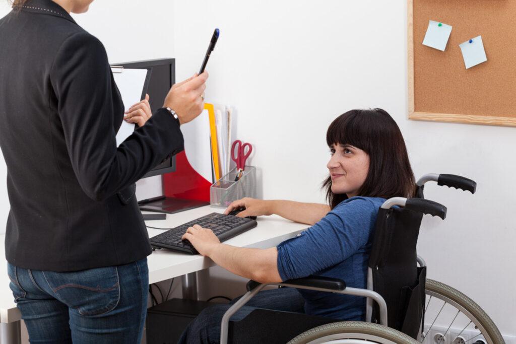 mulher cadeirante em sua mesa de trabalho conversando com outra mulher
