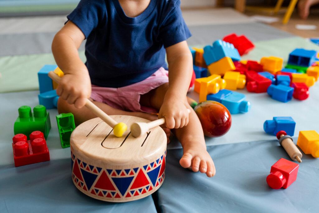 criança batendo em um tambor de brinquedo