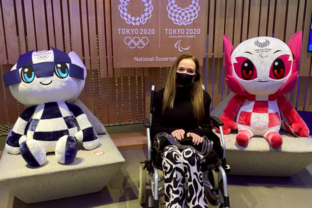 Beth Ribeiro está em sua cadeira de rodas, entre os mascotes dos jogos Olímpicos e Paralímpicos de Tokyo, na exposição da Japan House