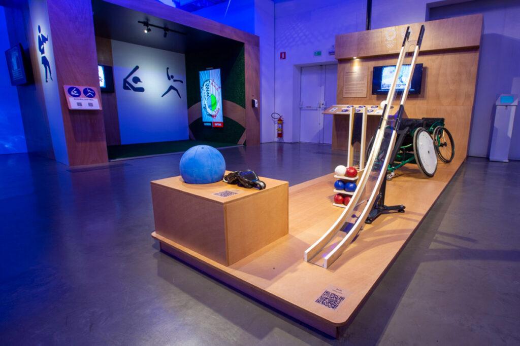 Um dos espaços da exposição, onde vemos a bola e óculos de Goalball, a canaleta e bolas da bocha, e uma cadeira de rodas esportiva.