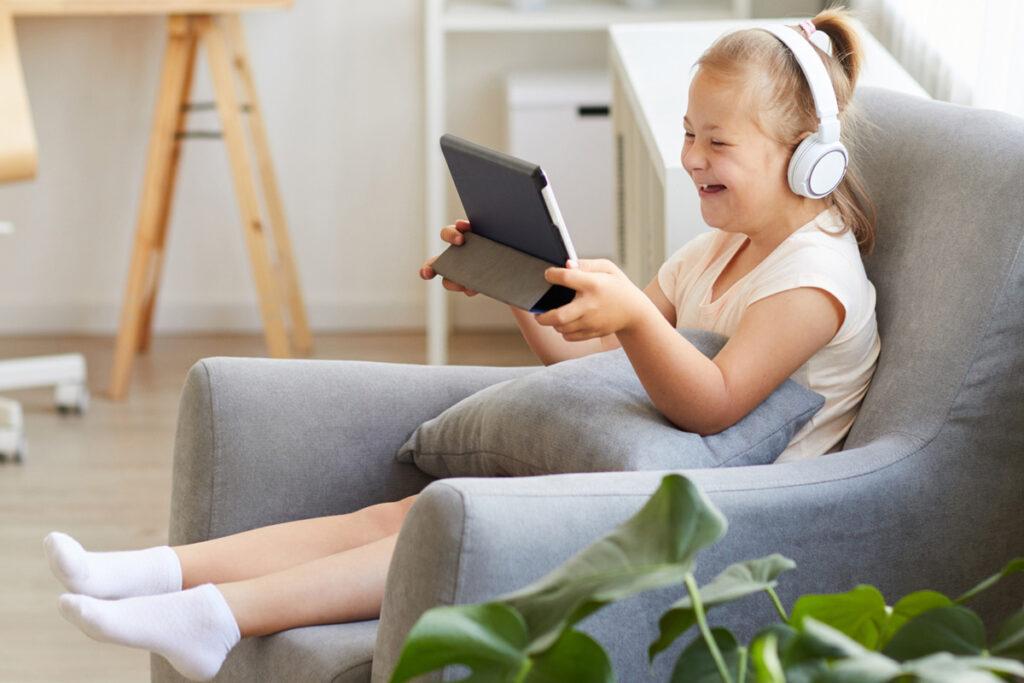 Criança sentada no sofá com fone no ouvido e um tablet na mão