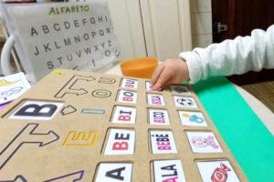 Criança fazendo atividade adaptada com letras, palavras e imagens