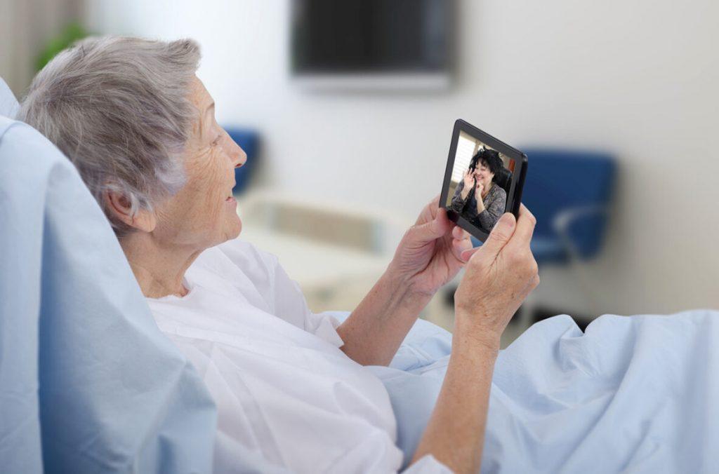 Idosa em uma cama de hospital fala com familiar através de videochamada