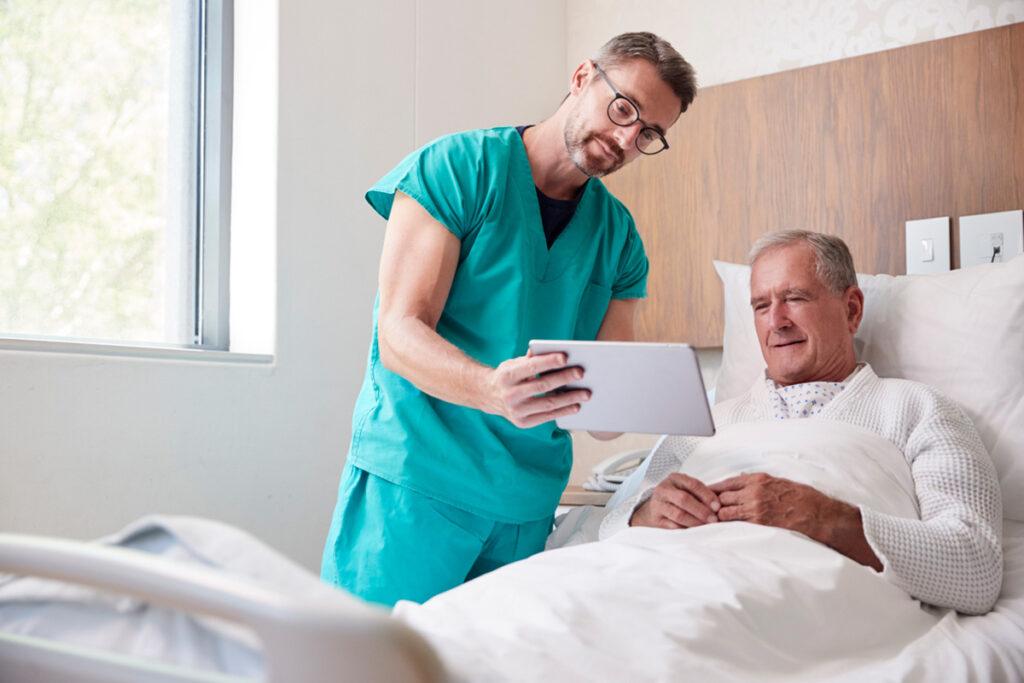 senhor idoso em leito de hospital realizando uma videochamada com um tablet a um familiar